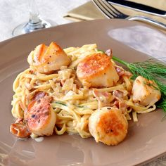 PAN SEARED SCALLOPS IN BACON FENNEL CREAM SAUCE 2 dozen large scallops 2 cloves garlic finely chopped 4 Tbsp extra virgin olive oil 1 cup whipping cream 1/2 cup seafood or chicken stock 1/4 cup white wine 6 slices crisp cooked bacon 2/3 cup finely chopped fennel (if fresh fennel is not available you can substitute ½ tsp ground fennel seed) Salt and pepper to taste 350 g package fresh cooked fettuccine pasta