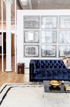 Navy velvet tufted sofa with black and white gallery wall, wood floors, and furry rug