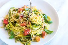 How to make our 20-minute zucchini pasta recipe with garlic, basil, tomatoes, and parmesan cheese.