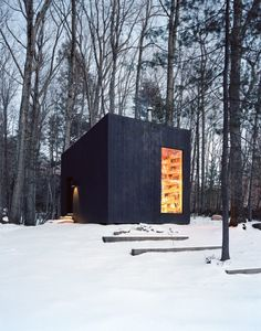 black wood shelter in a snowy forest