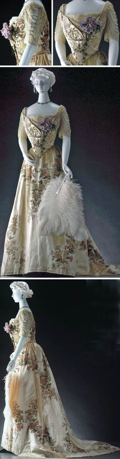Ball gown, Worth, ca. 1900. Cream silk satin self-striped in cut velvet, embossed with large floral motifs in cream, pink, & green. Boned bodice with square neckline & pointed waist at center front, trimmed with tulle, lace, & artificial flower at left breast. Lace sleeves falling to elbow with vertical line of rhinestones down upper arm. Fastens down back in V-shape with eyelets, lacing, & metal hook and eye. Gathered skirt with flat front. Powerhouse Museum