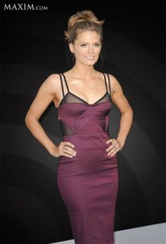 Stana Katic in a black and burgundy dress posing with her hands on her hips in front of a black background