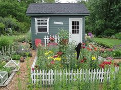 Adorable little shed with cottage garden in a picket fence.