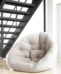 Unexpected guests are no sweat with this innovative futon chair. Part of the Fresh Futon line, this seat cleverly converts from a nest-shaped chair into a supportive semicircular mattress with a tufted design. Winner of the