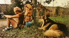 """Exhausted after a 40-mile day, a hiker collapses against a tree. As tired as his master, lays his dog Cooper. """"Time to pitch camp,"""" he yawns.  National Geographic - April, 1977"""