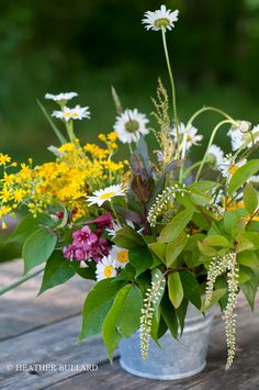 Simple arrangement of wildflowers in a bucket. Perfect for a summer picnic!