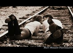 Rustic outdoor engagement photos on railroad train tracks