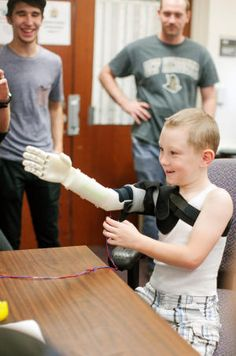 Six-year-old Alex Pring of Groveland, Fla., tries out the prosthetic arm created for him by a team of engineering students at the University of Central