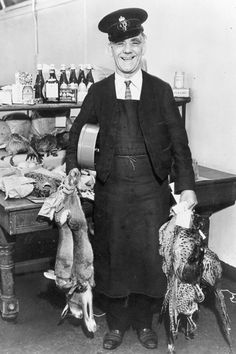 Returned parcels, 1938.  In 1936, Post Office rules stated that game, including rabbits, could be posted with nothing but a neck label as long as 'no liquid is likely to exude'. The postman here is holding some unusual mail found in the Returned Parcels section at Mount Pleasant sorting office, London.
