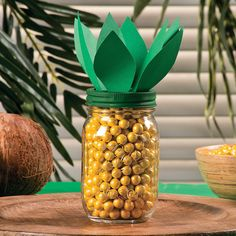 Pineapple Candy Jar Idea Create a tropical centerpiece your guests can grab candy out of! Easy to craft, this eye-catching candy jar centerpiece is great for your next backyard luau or tropical office party.  1. Paint the lid of a mason jar green and let dry. 2. Using green paper cut out about 6-7 oval shaped leaves. 3. Glue the leaves onto the painted mason jar lid. 4. Fill the jar up with yellow candy. 5. Put the lid on with the candy inside.