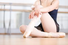 Close up shot of legs of sitting on the floor ballerina who wears white pointes