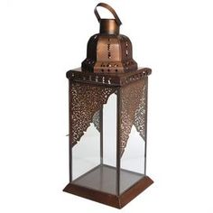 """Metal lantern with ajoure detail and glass panels.            Product: Lantern Construction Material: Metal and glass  Color: Bronze   Features:     Locking door  Top handle for easy maneuvering               Accommodates: (1) Candle - not included Dimensions: 20"""" H x 6"""" W x 6"""" D"""