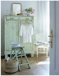 Seafoam green is a soft, cool, peaceful color for a bedroom. Nice touch of pink from the flowers in the white vase on top of the cupboard.