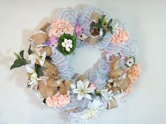 Sweet Bunnies and Spring Flowers on Glorious Bed of Decco Mesh. Sweet rabbits play with their baby bunnies on a full bed of light blue and interlaced ribbon deco mesh. Embedded are lilies, hydrangas, bits of greenery, as welll a two precious birds guarding a nest with five eggs. This bountiful wreath can grace a door all the way into summer.