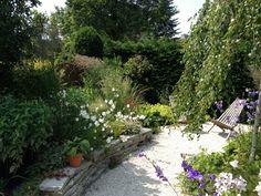 Natuurlijke tuin. Tegels zijn hergebruikt voor het stapelmuurtje.