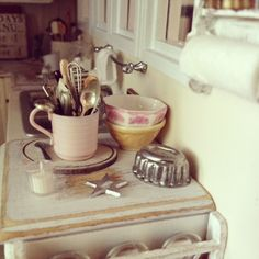 Miniature scene, assorted utensils and bowls. Glass of milk and cookie cutters.