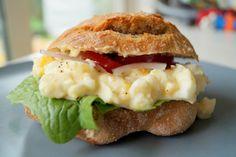 Sandwich med æggesalat. En koldehævede bolle med rugmel fyldt med salatblade, tomat, rødløg og hjemmelavet æggesalat - en super lækker frokost sandwich.