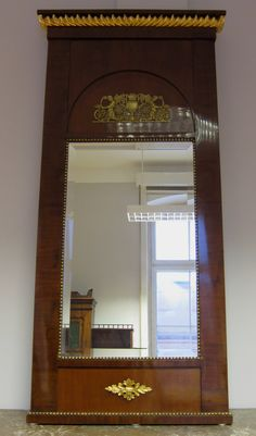 Empire Spiegel mit Bronzeapplikationen Französischer Spiegel aus dem kaiserlichen Empire-Zeitalter. Er wurde um 1810 aus feinstem Mahagoni, massiv und furniert, gefertigt und bezaubert durch seine klassizistische Gliederung und erhabene Ausstrahlung.  Kennung : Nr. 037