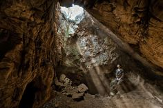 """Sunlight falls through the entrance of Rising Star cave, near Johannesburg. A remote chamber has yielded hundreds of fossil bones—so far. Says anthropologist Marina Elliott, seated, """"We have literally just scratched the surface."""""""
