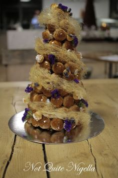 I like the color of the cream puffs, that they are still formed, and their sheen. Also, I like the spun sugar interspersed with flowers.
