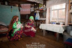 Image of irina & vera purgurchina, two khanty women, chat while softening pieces of reindeer skin inside a log cabin on the bank of the synya river. yamal, western siberia, russia by ArcticPhoto