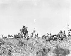 Lieutenant Ralph Barnes of Arlington, Va., platoon leader, 1st Platoon, Co. C, 15th Infantry Regiment, 3rd Infantry Division, throws a hand grenade at Chinese Communist positions, as UN troops launch an offensive attack against the Communist near Uijong-Bu, Korea.   23 March 1951. Korea.   Signal Corps Photo #8A/FEC-51-9245 (Welter)