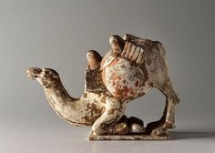 A PAINTED POTTERY FIGURE OF A KNEELING CAMEL China, Tang dynasty (618-906). Width 24.5 cm. Pottery tomb figure depicting a camel kneeling on its anterior legs. The realistically depicted animal stretches its long neck forward, on its back between the two humps one can see bags with a load. Over the figure's entire surface, traces of the red and brown polychrome can be seen. This is a typical tomb figure from the Tang dynasty (618-907).