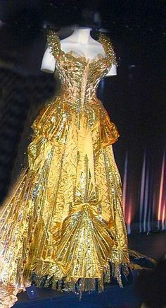 Material: Yellow satin; golden yellow satin; metallic thread embroidery; paillettes and beads; midnight blue velvet; yellow tulle with applied tinsel; tinsel and looped cord edging; glass pearls; fringe.  created by Maison Worth
