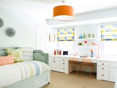 With classic white walls, this teen bedroom is brought to life with a cheery orange pendant, green upholstered daybed and patterned Roman shades.