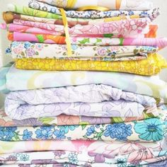 lovely big pile of vintage florals I like the vintage sheets best.  Easy and inexpensive way to cheer up a room.