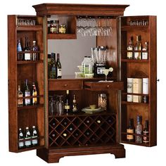 "This Hide-A-Bar""¢ cabinet features paneled doors with inset panels of Ash Burl veneers in a parquet pattern framed with decorative moldings and oversized antique brass finished door knobs. Stores up to 22 bottles of wine, with a generous amount of room in the doors for liquor storage. An upper fixed shelf may hold glasses and tumblers. The cabinet is finished in Hampton Cherry with light distressing on select hardwoods and veneers. Wooden stemware racks. Front locking doors. The left door is…"