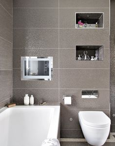 This modern shimmering bathroom is the height of luxury thanks to its 3D-effect tiling and alcove shelving. An integrated television also gives the bathroom an extra special something, hinting at long, luxurious baths! The collection of glass perfume bottles in one of the alcove shelves is an interesting and eyecatching way to accessorise using everyday items.