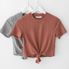 Mock neck crop top with front knot detail and short sleeves. Made with soft and lightweight ribbed knit material that has a good stretch. Available in heather grey or rust. - 72% Polyester 23% Rayon 5
