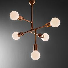 Retro-futuristic chandelier inspired by mid-century modern design - here shown in rose gold copper metal finish, with sphere, milk bulbs