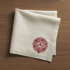 Red Birds Napkin | Crate and Barrel  Carly Dodsley's delicately drawn turtledoves take inspirational flight from the traditional carol, beautifully embroidered in red on linen. Designed by Carly Dodsley100% linenEmbroideredMachine wash cold, dry low; warm iron as neededDo not bleachMade in India.