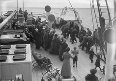 Passengers on board the Cunard cruise liner Franconia engage in a friendly game of tug-of-war on deck, with delighted onlooking children