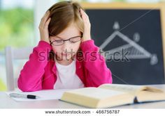 Stressed and tired schoolgirl studying with a pile of books on her desk. Child feeling unhappy about going back to school.