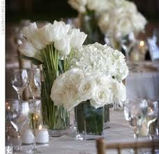 different white flowers on table at different heights, surrounded by candles