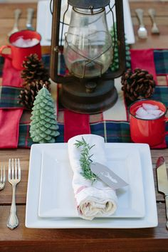 Sprigs of rosemary are the perfect accent for a holiday table setting, and we can't help but love the little pops of plaid ribbon, used to create a table runner. Create your own table runner from ribbon by visiting our design blog, How to Decorate.