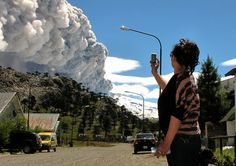 A woman takes a picture with her mobile phone from Caviahue, Neuquen province, Argentina, some 1500 km southwest of Buenos Aires, of the Copahue volcano spewing ashes on December 22, 2012. The authorities of Chile and Argentina issued yellow alerts due to the eruption of the Copahue volcano, placed in the border between both countries. (Photo by Antonio Huglich/AFP Photo)