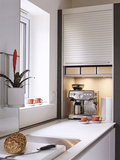 Cupboards with shutter doors are perfect for neatly concealing a coffee machine and drinks station.Sapphire Spaces l bulthaup Exeter
