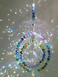"I created this suncatcher with 76 5mm Swarovski Bicone crystals in shades of Lilac, Lavender, Blues and Greens. The outer circle measures approximately 2 1/2"" and the inner circle swings freely as you can see in my photos. The center crystal is an exquisite 20mm Swarovski Strass faceted Crystal Ball. The entire length of the suncatcher, including the plated hanging ring, is 6 1/2""."