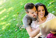 Happy couple working on a laptop computer outdoors