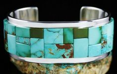 Tommy Jackson Rare High Grade Royston Turquoise Inlay Bracelet #TommyJackson #Cuff Incredible square cuts of high grade natural Royston turquoise with vibrant shades of green and blue are inlaid with precision onto a heavy sterling silver shank and raised above it. Tommy Jackson has inlaid the stones side by side, so they must be precisely hand cut. The tremendous lapidary skill is clearly evident and is outstanding. Surely one of his finest, the bracelet glows with intensity on the wrist.