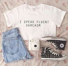 White graphic crop top, light wash shorts and studded converse.