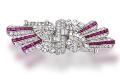 An art deco diamond and ruby double clip brooch, circa 1930 each designed as a transitional, round brilliant and baguette-cut diamond spray, accented by calibré-cut rubies; estimated total diamond weight: 19.00 carats; mounted in platinum; length: 3 1/2in.