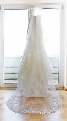 beautiful wedding dress with long lace bridal veil on window by © Radmila Kerl wedding photography munich wunderschönes Brautkleid / Hochzeitskleid mit langem Spitzenschleier