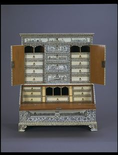 Lookin' like a drop-front desk to me!  Miniature bureau-cabinet   Place of origin:        Vishakhapatnam, India (made)      Date:        18th century (made)      Artist/Maker:        Unknown (production)      Materials and Techniques:        Wood veneered with ivory, engraved and highlighted with lac