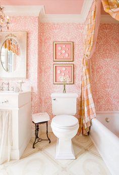 Bagno in una delicata tonalità di rosa. Mi piacciono i quadretti e la tenda che chiude la vasca.