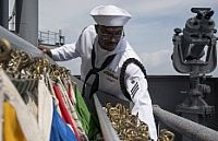 Quartermaster Seaman Rodney Cobia, from Charlotte N.C., stows flags on the signal bridge of the Nimitz-class aircraft carrier USS George Washington (CVN 73) as the ship departs Fleet Activities Yokosuka, Japan for its 2015 patrol. George Washington is making its departure from Japan after serving as the U.S. Navy's only forward-deployed aircraft carrier for seven years.